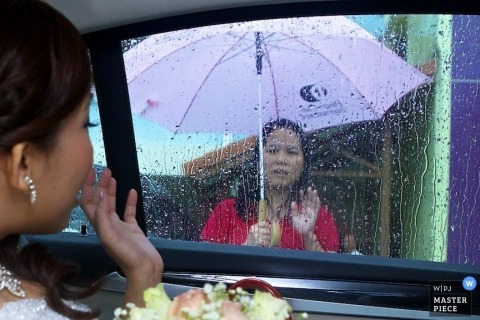 Singapore wedding photography - Asia photo of the bride waving goodbye to her mother through a rain streaked window