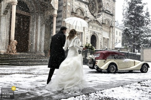Bergamo wedding photographer captured this photo of a bride and groom walking to their car in the gently falling snow