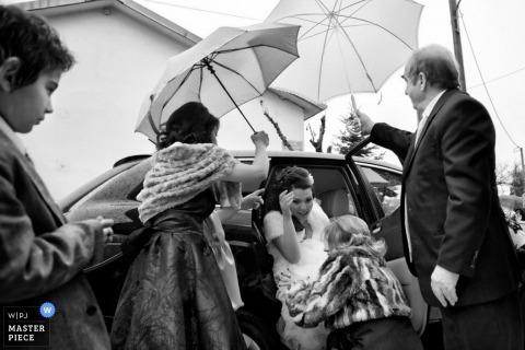 De huwelijksfotograaf van Thessaloniki ving deze zwart-witte foto van de bruid die uit de auto door gasten wordt geholpen die paraplu's houden tijdens een regenonweer