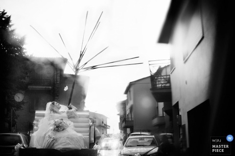 Arezzo wedding photographer captured this black and white photo of the bride struggling with a large umbrella during a storm