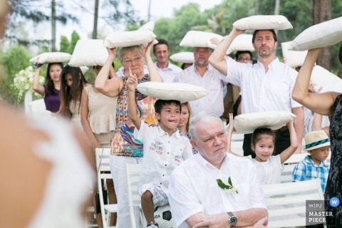 London wedding photographer captured this photo of wedding guests using chair cushions to protect them from the elements