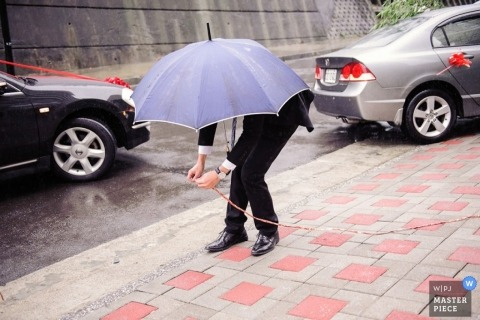 Taipei wedding photographer captured this photo of a wedding guest sheltering under an umbrella to shield the rain