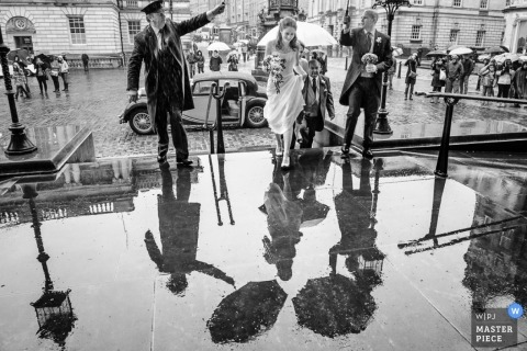 Scotland wedding reportage photographer captured this photo of the bride and grooms reflection in a puddle as they walk to their wedding on a rainy day in the UK