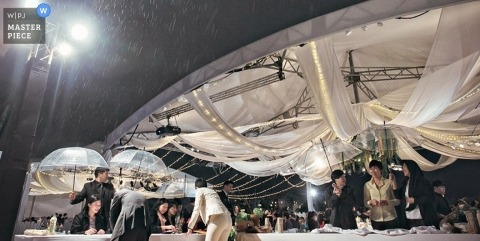 Taipei wedding photographer captured this photo of guests taking shelter under umbrellas and the wedding tent during a rain storm