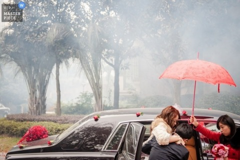 Jiangsu wedding photographer captured this photo of the bride getting help with an umbrella during a rainstorm