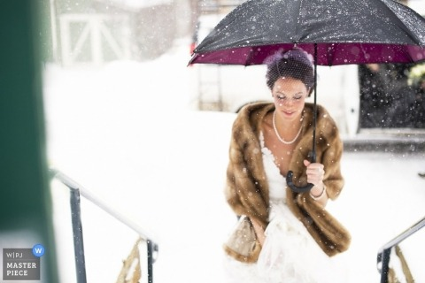 A wedding photographer captured this photo of a bride carrying an umbrella while walking through the rain