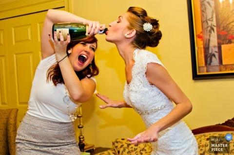 Outerbanks-huwelijksfotograaf ving deze foto van de bruid die wat hulp krijgt die champagne van de fles drinkt