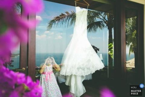 Der Hochzeitsfotograf von Koh Samui hat dieses Foto eines kleinen Mädchens aufgenommen, das das Hochzeitskleid durch ein großes Glasfenster bewundert