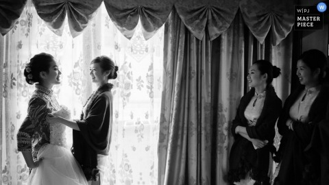 Hangzhou City wedding photographer captured this black and white photo of the bride showing off her dress as she gets ready for the ceremony