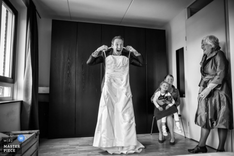 Overjissel wedding photographer captured this humorous photo of the groom trying on the wedding dress in the Netherlands