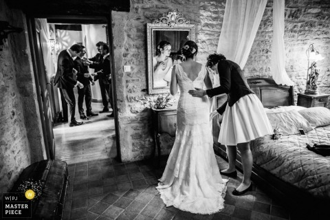 Montpellier wedding photographer captured this black and white photo of the bride checking the mirror one last time and a bridesmaid checking her dress before they head to the Hérault ceremony