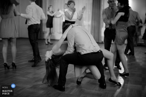 Malopolskie wedding photographer captured this black and white photo of a wedding guest being dipped on the dance floor in Poland