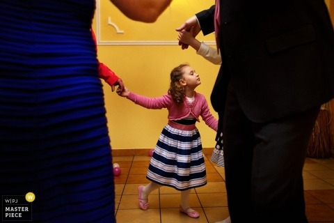Krakow wedding photographer captured this photo of a little girl dancing with other wedding guests at the reception