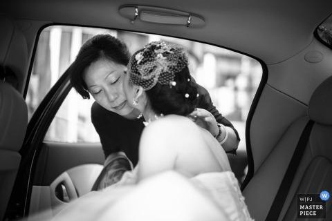 Un photographe de mariage a capturé cette photo en noir et blanc de la mariée embrassant sa mère sur la joue avant que la voiture ne parte pour se rendre à la cérémonie