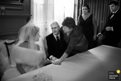 Le photographe de mariage d'Atlanta a capturé cette image en noir et blanc émotionnelle de la mariée parlant avec ses parents avant la cérémonie alors qu'ils se tenaient la main