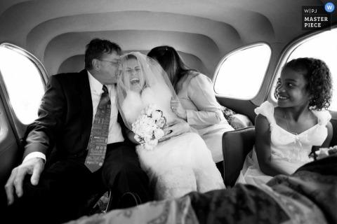 Photographe de mariage à Paris, cette joyeuse photo en noir et blanc de la mariée en train de rire alors que son père l'embrasse sur la joue