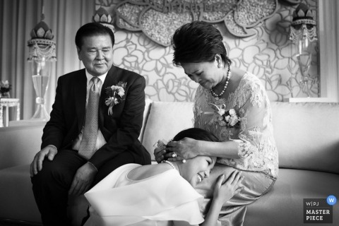 Bangkok wedding photographer captured this black and white photo of the bride kneeling before her parents before her wedding ceremony