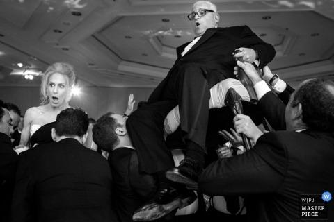 El fotógrafo de bodas de San Diego capturó esta foto en blanco y negro de la novia y el novio que fueron izados en sillas sobre la pista de baile