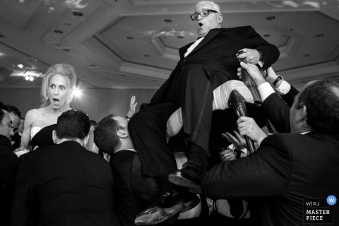San Diego wedding photographer captured this black and white photo of the bride and groom getting hoisted in chairs above the dance floor