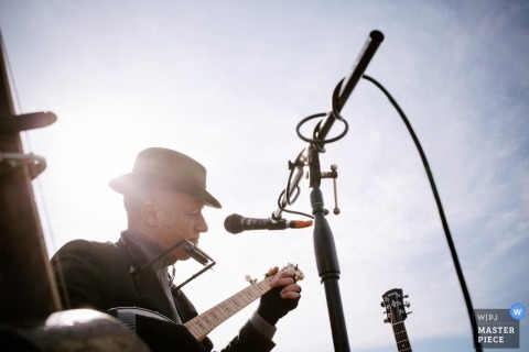 Dorset wedding photographer captured this photo of a musician playing guitar under a sunny sky at the wedding reception