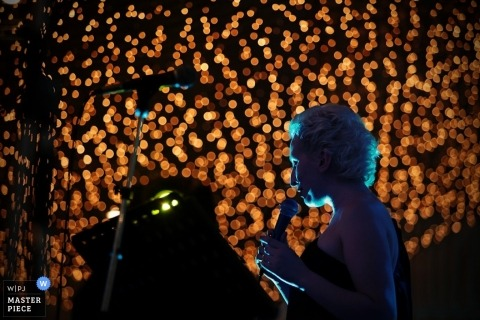 Moscow wedding photographer captured this photo of a guest giving a speech in front of a wall of lights
