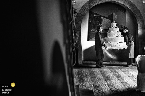 Arezzo wedding photography - Tuscany black and white photo of the caterers carrying in a giant wedding cake