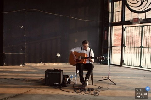 New Jersey wedding photographer captured a musician playing an acoustic guitar at an industrial reception location