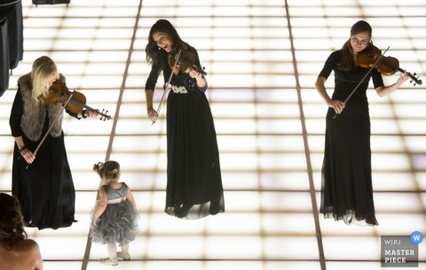Chicago wedding photographer captured this photo of a girl dancing with a trio of violinists on a lit up stage