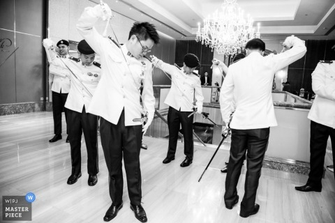 Singapore wedding photographer captured this black and white photo of the groomsmen doing a ritual with swords before the ceremony