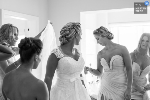 New South Wales wedding photographer captured this black and white photo of the bridesmaid helping the bride into her dress in Australia