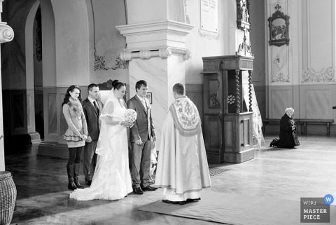 Lithuania wedding photographer captured this black and white photo of the bride and groom saying their vows at the ceremony
