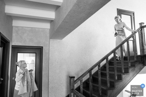 A wedding photographer captured this black and white photo of the bride walking down a flight of stairs towards her mother