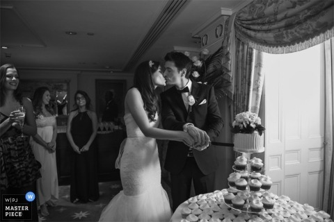 London wedding reportage photography - England black and white photo of the bride and groom kissing before cutting the cake