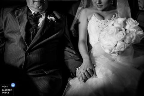 Minas Gerais wedding photographer captured this black and white photo of the bride and her father holding hands on the ride to the ceremony