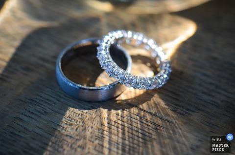 A wedding photographer captured this photo of the wedding bands resting on a piece of wood as the light makes them sparkle
