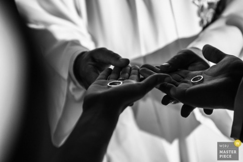 Bahia wedding photographer captured this black and white photo of the bride and groom holding their rings in the palm of their hands