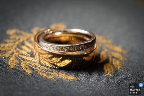 Il fotografo di matrimoni di Atlanta ha catturato questa foto delle fedi nuziali appoggiate su tessuto ricamato