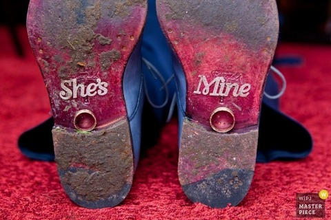 "Zuid Holland wedding photographer captured this detail shot of the wedding bands resting on a the soles of boots that say, ""She's Mine."""