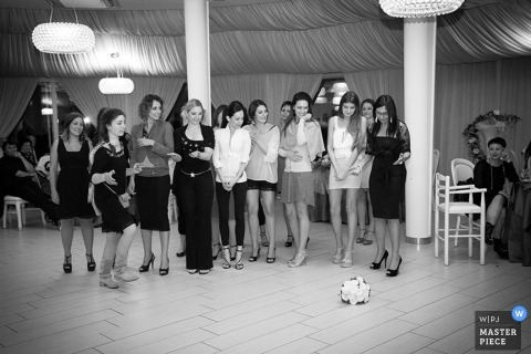 Documentary Wedding Photograph in Latina | Image contains: black and white, bouquet toss, guests, reception