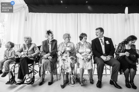 Documentary Wedding Photography in London | Image contains: wedding guests, black, white, chairs, indoors