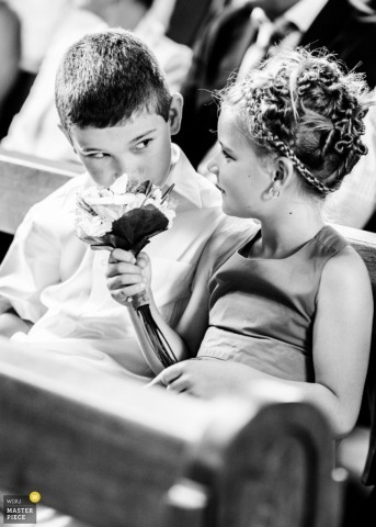 Switzerland Documentary Wedding Photographer | Image contains: flowergirl, boy, flowers, pews, ceremony, black, white