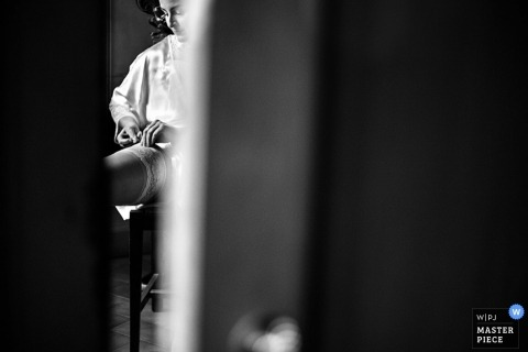 Wedding Photographer in Arezzo | Image contains: black and white, bride, getting ready, garter, door