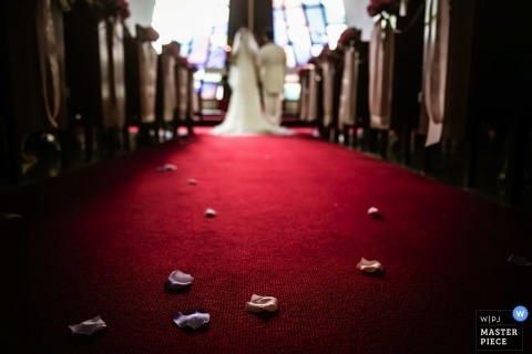 Wedding photograph from Hong Kong | Image contains: pews, ceremony, flower pedals, red carpet, bride, groom