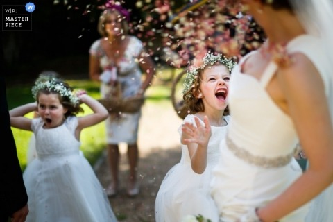 Wedding Reportage Photographer in Hertfordshire   Image contains: confetti, color, bride, flowergirls, outdoors