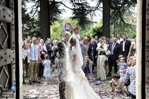 Bergamo Wedding Photographer | Image contains: kiss, color, rice, wedding quests, couple, doors