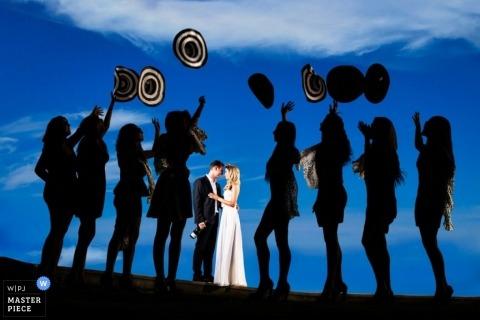 Tel Aviv Wedding Photography | Image contains: portrait, hats, sunset, blue, couple, bridemaids, light