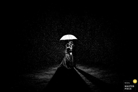 Wedding Photographer in North Rhine-Westphalia | Image contains: portrait, umbrella, couple, kiss, night, light, blacke, white