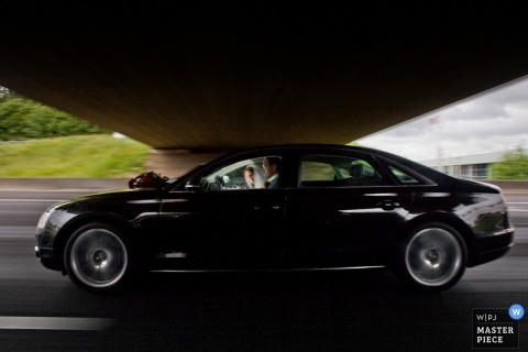Zuid Holland Wedding Photography | Image contains: car, highway, color, bride, groom, outdoors, blur, slow-shutter
