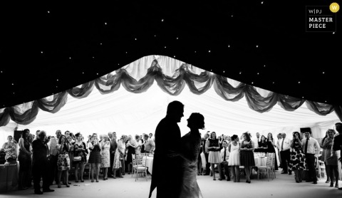 Greater Manchester Documentary Wedding Photographer   Image contains: reception, tent, black, white, groom, bride, wedding guests