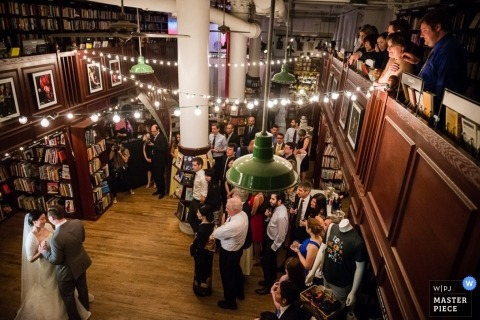 Manhattan Documentary Wedding Photographer | Image contains: reception, wedding guests, indoors books, lights